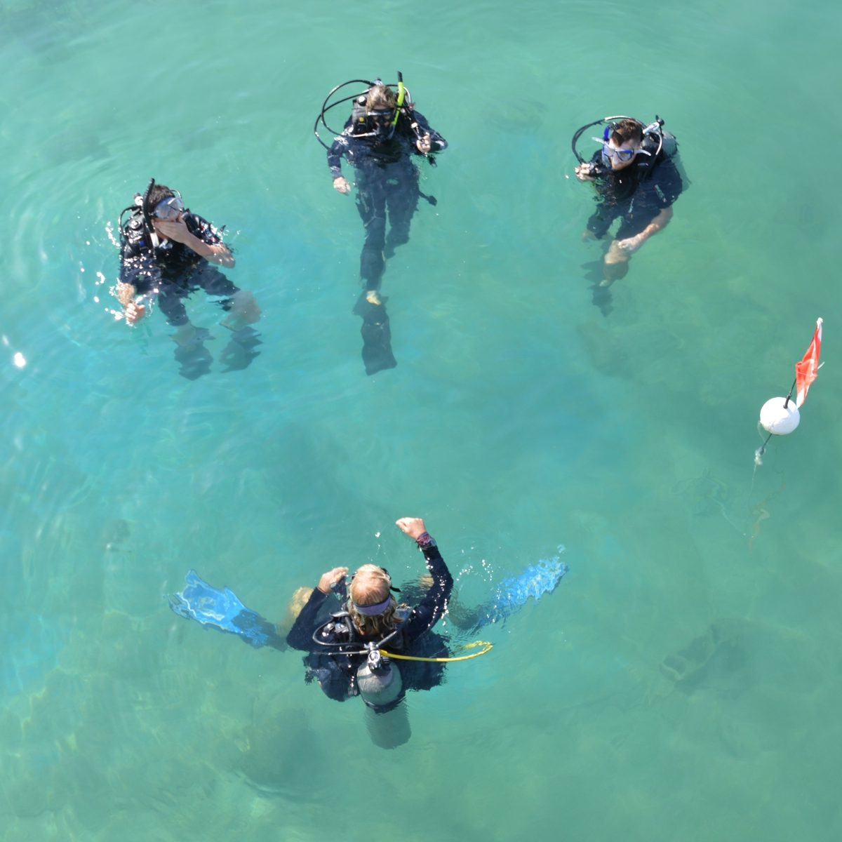 Scuba instructor teaching three PADI Open Water Diver students in the sea